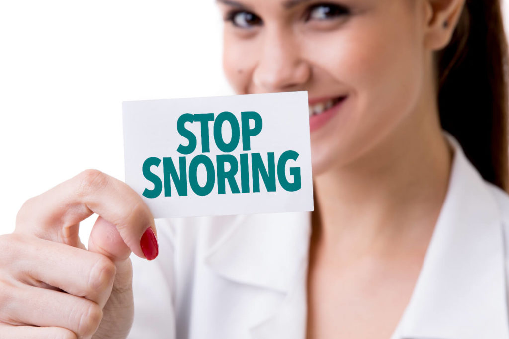 women-holding-stop-snoring-sign