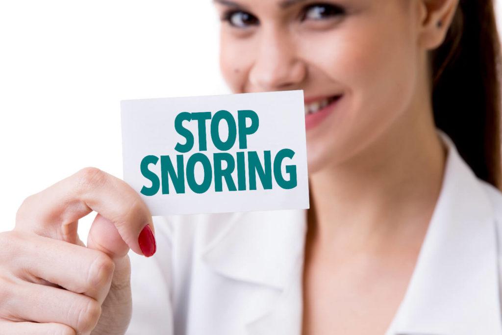 women-holding-stop-snoring-sign